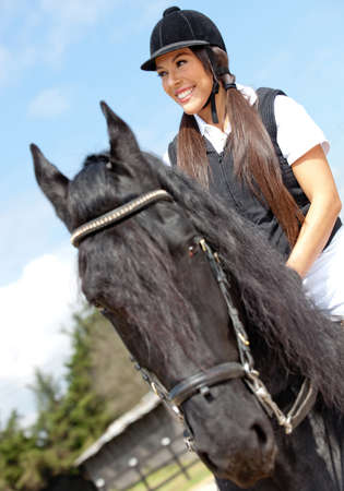 Happy female jockey riding a horse outdoors and smiling  photo