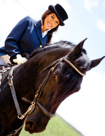 Elegant woman horseback riding outdoors and smiling photo