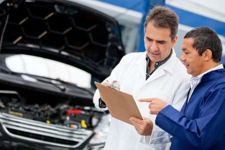 engineering clipboard: Male mechanics talking about fixing a car