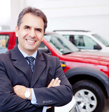 Business man working at a car dealer smiling  photo