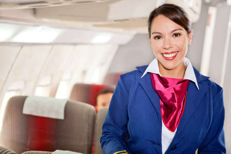 Beautiful flight attendant in an airplane cabin smiling photo