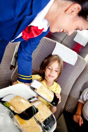 air hostess: H�tesse de l'air de servir des aliments � un enfant dans l'avion Banque d'images