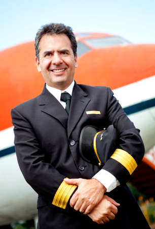 Confident pilot smiling with an airplane at the background Stock Photo - 12619664