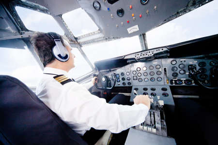 pilot: Pilot in an airplane cabin flying a plane