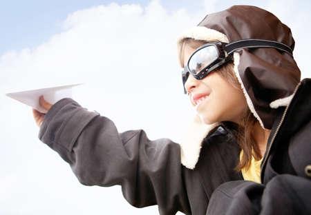 piloto: Boy como un piloto de estilo antiguo sosteniendo un avi�n de papel