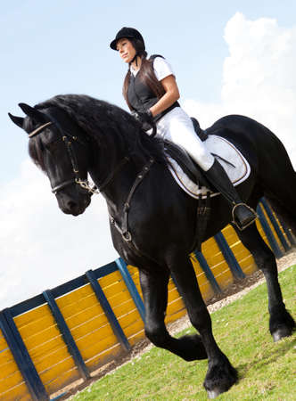 Female jockey horseback riding a black horse  photo