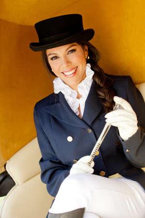 ringmaster: Elegant female jockey wearing a hat in a carriage