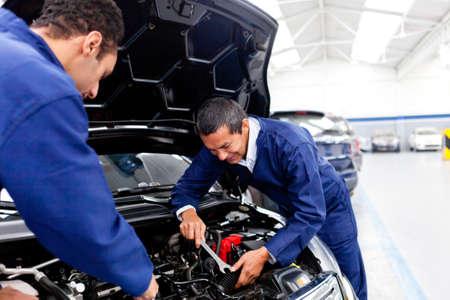 auto monteur: Man mechanica aan de garage de vaststelling van een auto Stockfoto