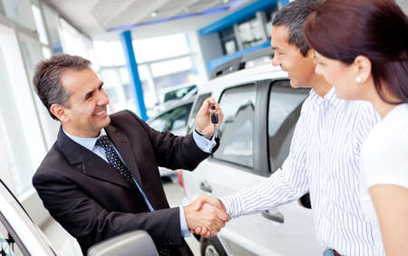 Couple buying a car and salesman handling keys  Stock Photo - 12619677