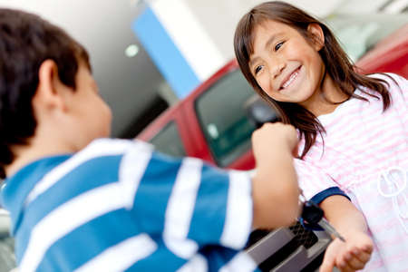 Happy kids playing with car keys at a dealership photo