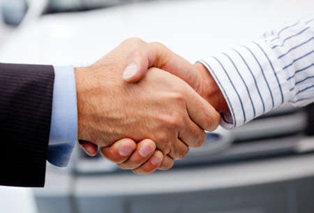 car dealers: Business handshake to close the deal after buying a car