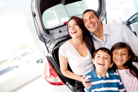 Happy family at the dealership buying a car photo