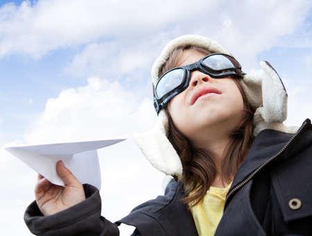 piloto de avion: Chico joven piloto de la celebraci�n de un avi�n de papel, mirando al cielo