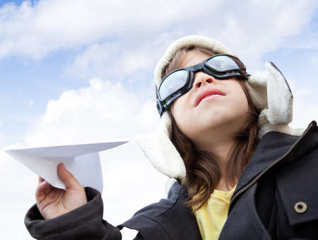 Young boy pilot holding a paper airplane looking at the sky photo
