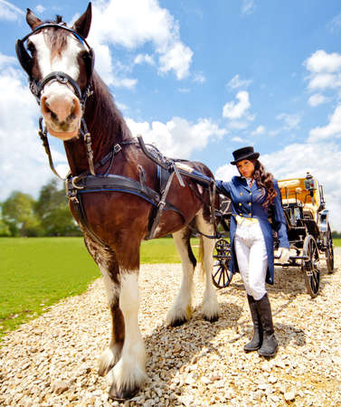 ringmaster: Beautiful female horse carriage driver wearing an outfit Stock Photo
