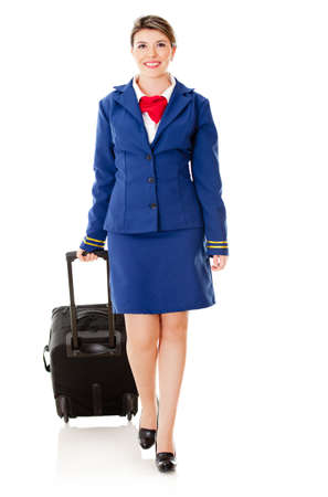 Beautiful air stewardess walking with bag – isolated over white photo