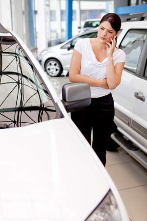 people buying: Woman thinking about buying a car but looking lost  Stock Photo
