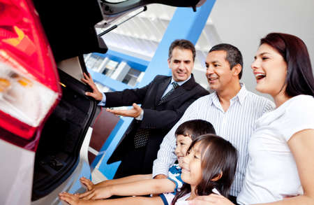 car dealers: Family at the dealership buying a new car Stock Photo