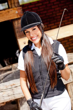 whip: Beautiful female jockey in uniform with a whip