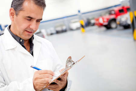 car garage: Male mechanic working at a car garage and taking notes  Stock Photo
