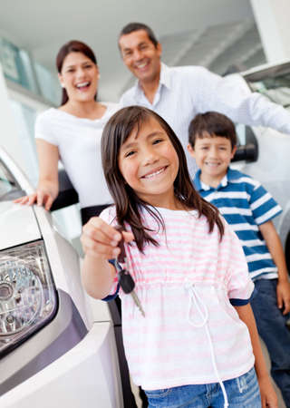 car dealers: Happy girl holding keys to new family car