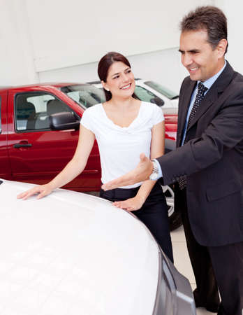 Salesman showing cars to a woman for her to buy photo