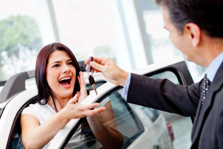 buying a car: Salesman handling keys to a woman after buying a car