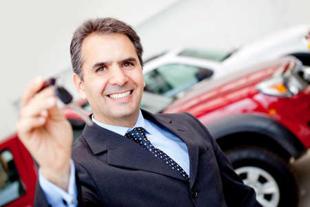 Business man at the dealership buying a car holding keys photo