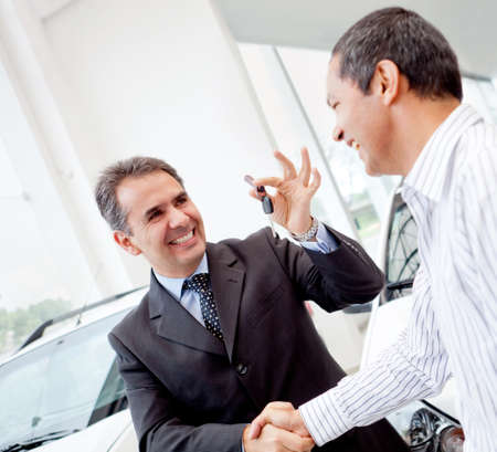 seller: Salesman handling keys to a man after buying a car