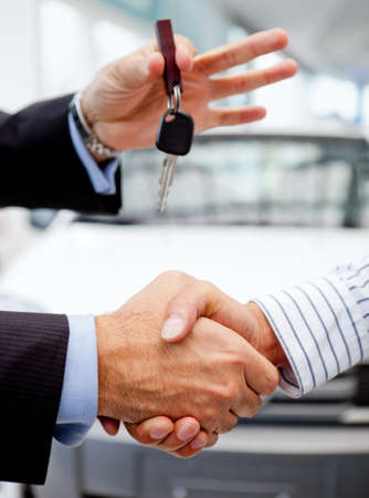 buying a car: Handshake after buying a car and handling keys Stock Photo
