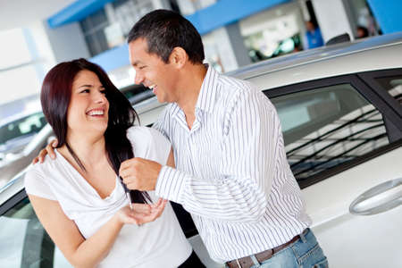 Couple at the dealer buying a car and looking happy photo