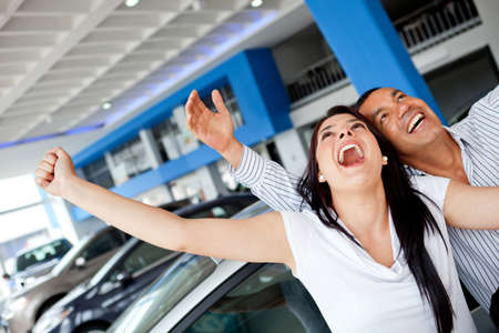 Excited couple buying a car at the dealer with arms up  photo