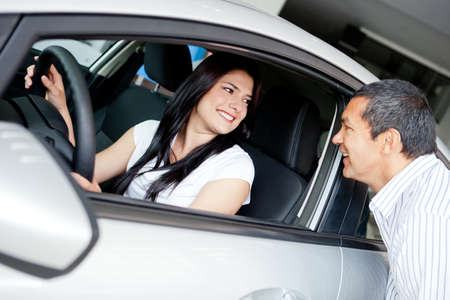 car dealers: Woman driving her new car at the dealer  Stock Photo