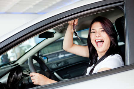 people buying: Excited woman buying a car and holding keys