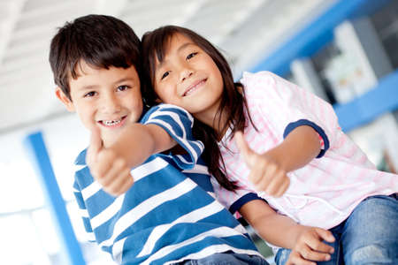 latin woman: Happy kids with thumbs up and smiling