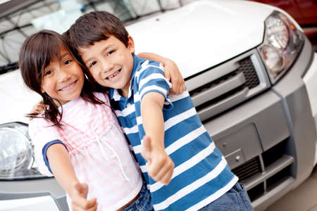 Happy kids buying a car at the dealer with thumbs up photo