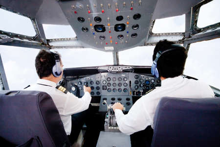 Pilots sitting in the cabin flying an airplane  photo