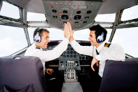 aviators: Pilots giving a high-five in an airplane cabin