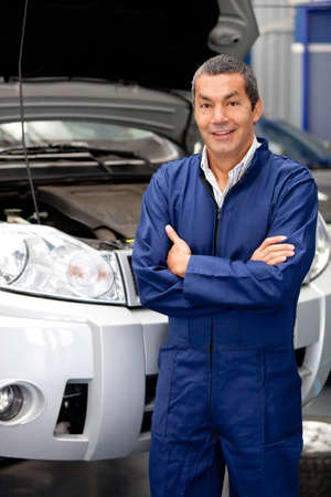 car garage: Man working at a car garage fixing engines  Stock Photo