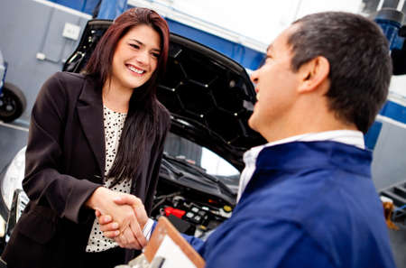 car in garage: Happy woman handshaking with a mechanic after a good service  Stock Photo