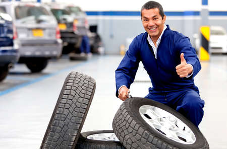 car garage: Mechanic at a car garage working on wheels with thumbs up  Stock Photo
