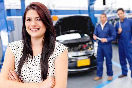 auto garage: Woman at the mechanic getting her car fixed  Stock Photo