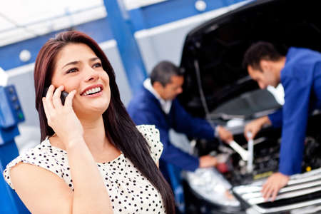 broke: Woman calling mechanic after her car broke down Stock Photo