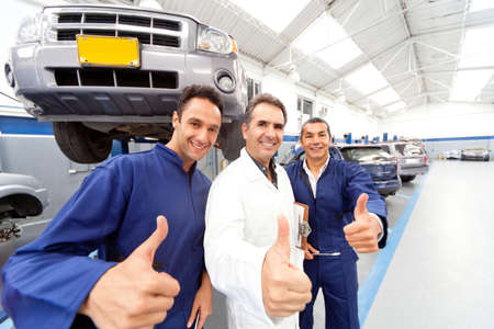 car in garage: Happy group of mechanics with thumbs up at a car garage Stock Photo