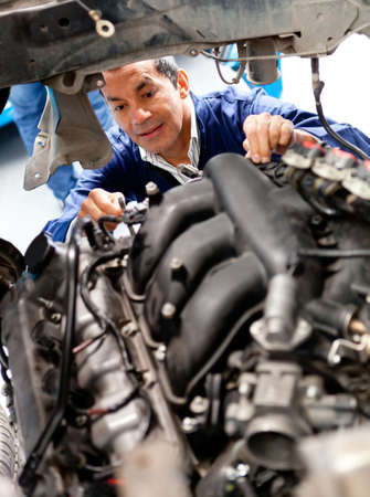 Male mechanic at a garage fixing a cars engine photo