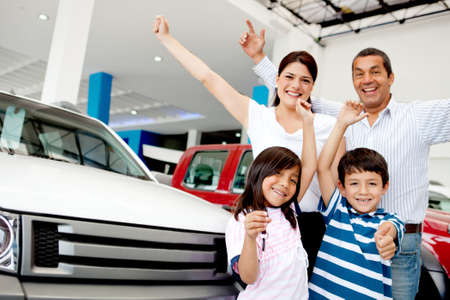 Happy family with arms up celebrating having a new car photo