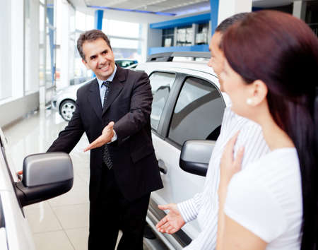 car dealers: Couple with dealer looking for a new car to buy Stock Photo