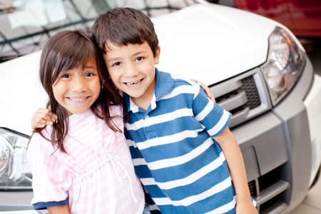 Two kids at the dealer buying a family car  photo