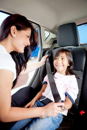 enfant banc: Femme aidant une jeune fille pour fixer sa ceinture de s�curit� dans une voiture