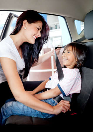seat belt: Mother helping to fasten seat belt to her little girl in a car
